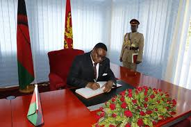 The president AP Mutharika signing the document